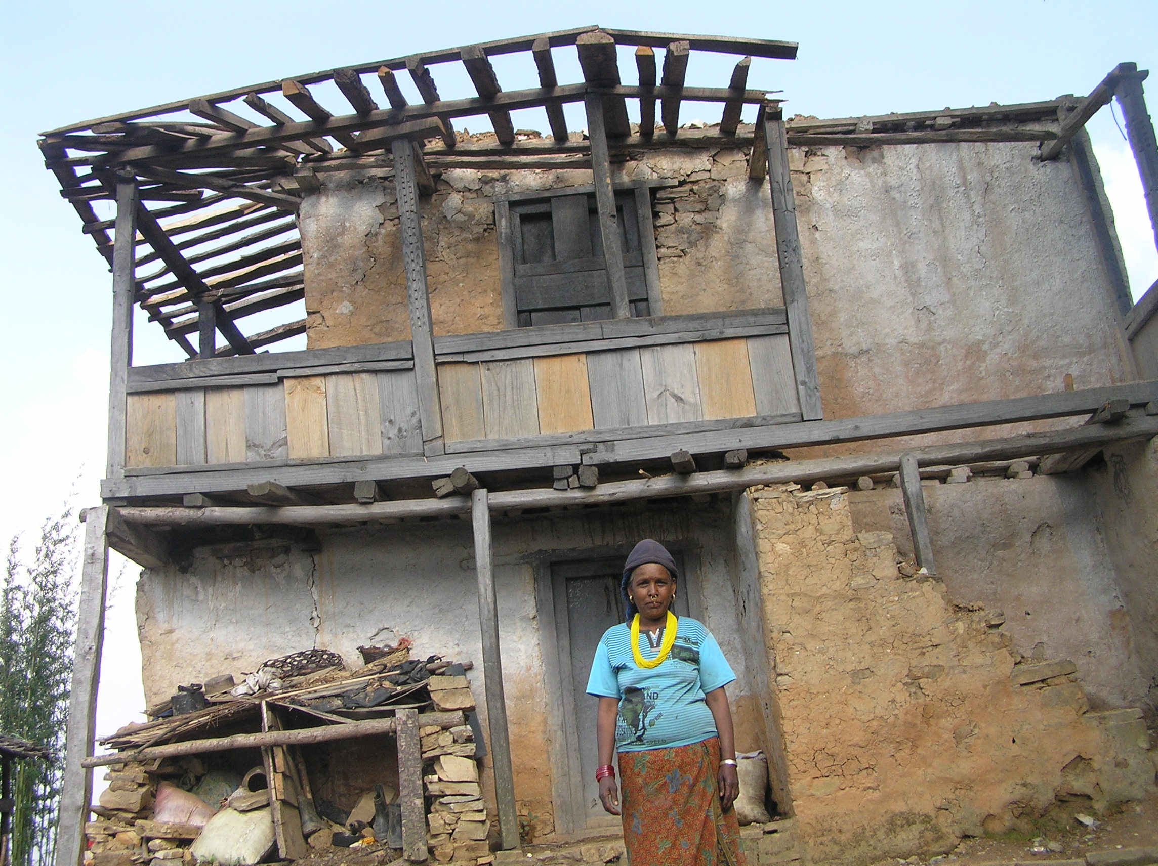 A-Dalit-lady-stand-infront-of-her-damaged-house-by-April-25-earthquake-at-Phalate-Okhaldhunga-Nepal