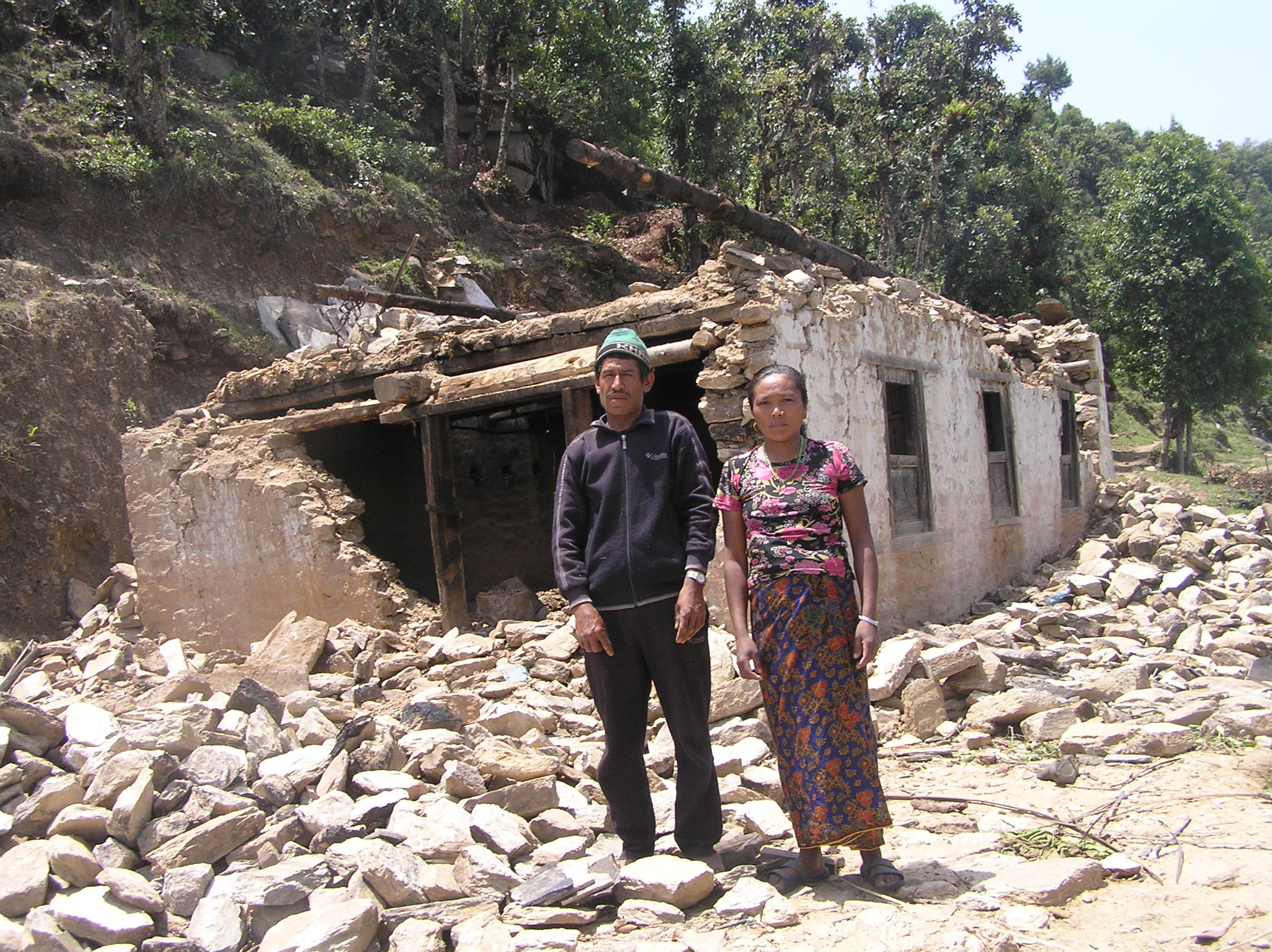 Dhan-Bahadur-Taamng-and-his-wife-stands-infront-of-damaged-house.