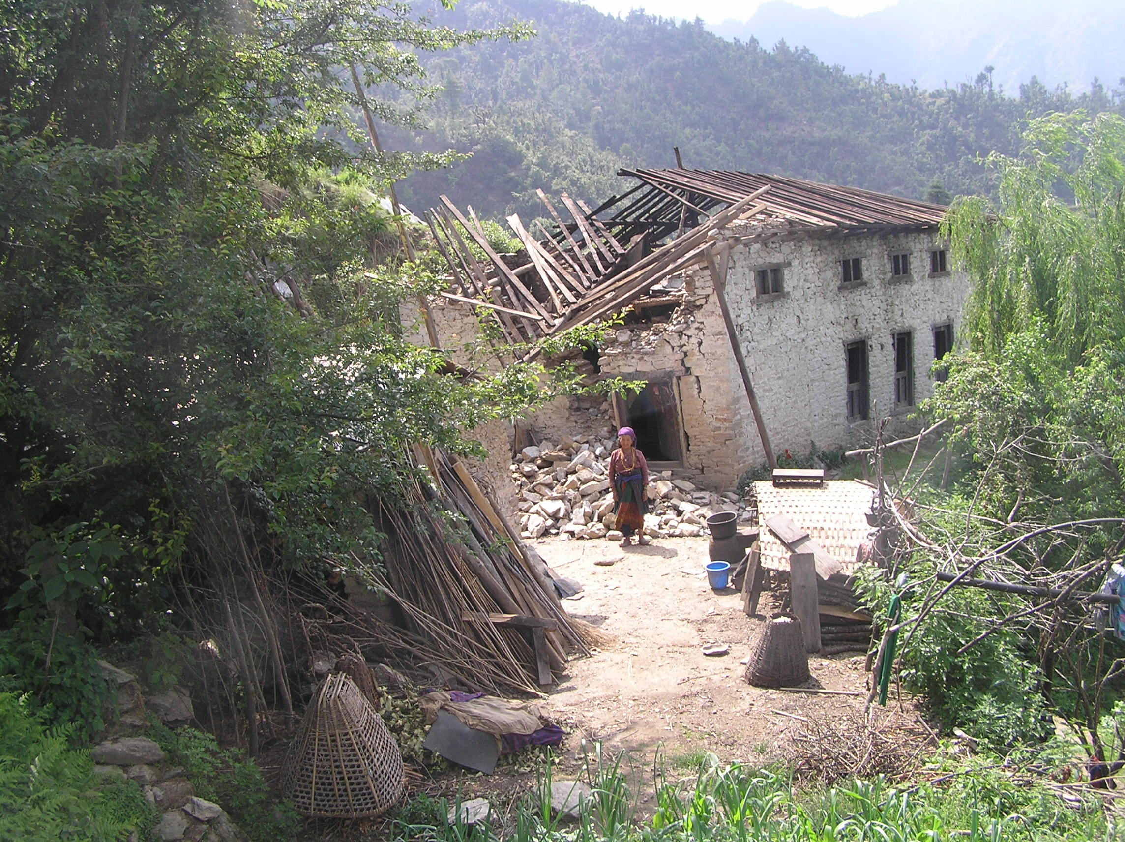 Garma-Sherpas-wife-stands-infront-of-her-damaged-house.
