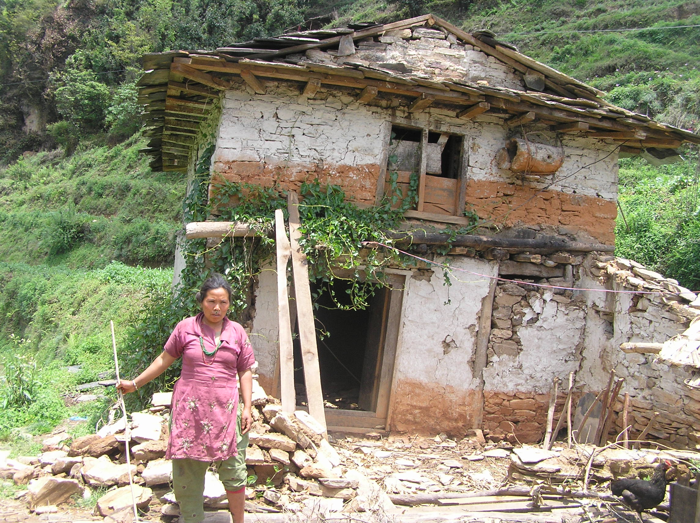 Phulmaya-Tamang-of-Kopche-stands-infront-of-her-damaged-house-who-was-also-injured-during-earthquake